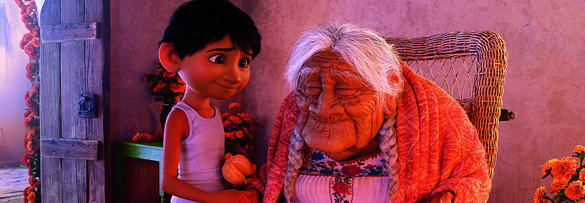 The main character from Disney-Pixar's Coco, standing next to his great grandmother.
