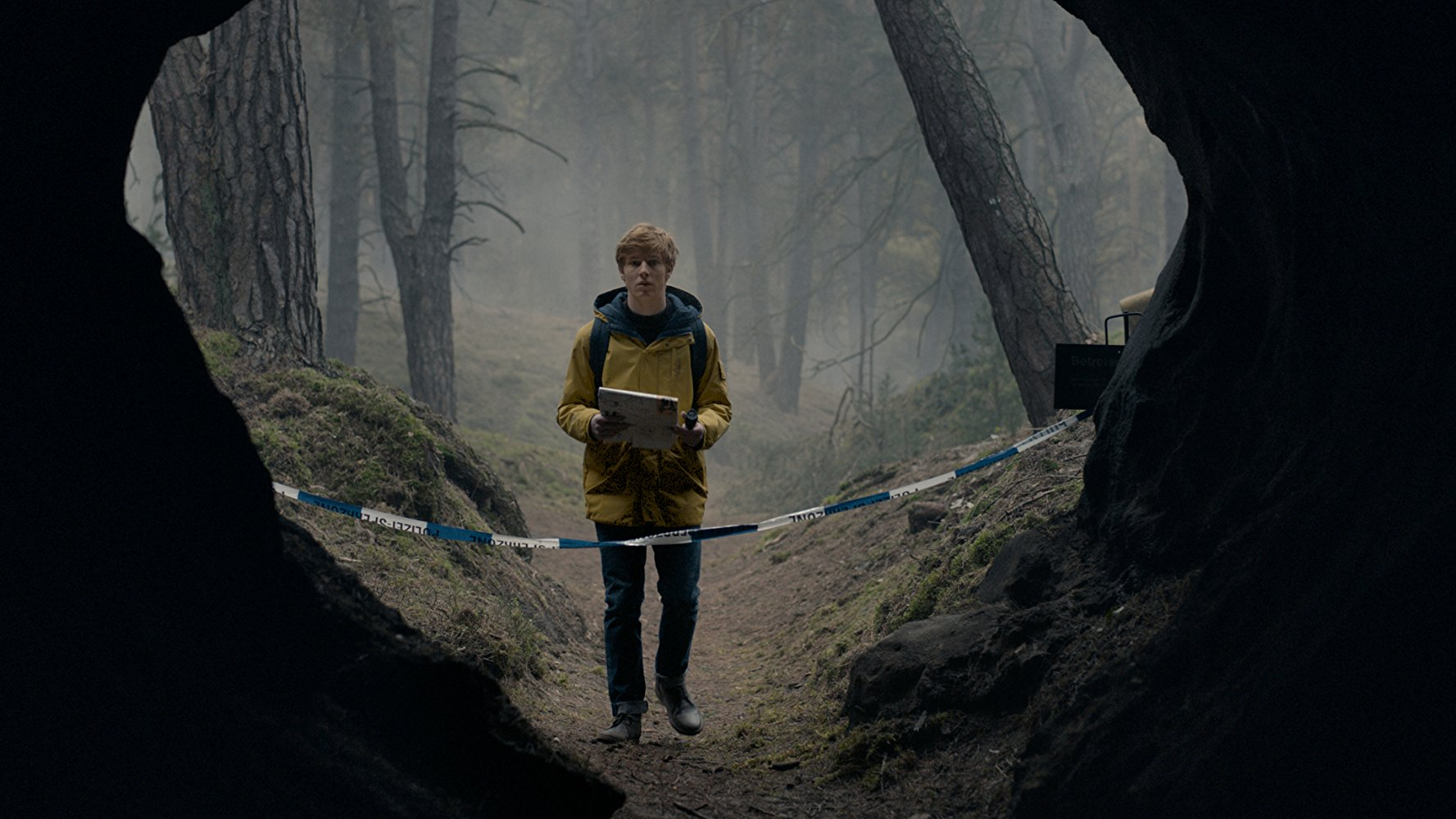 A teenaged boy standing in front of a cave that is blocked by police tape. He appears to be in a foggy forest.