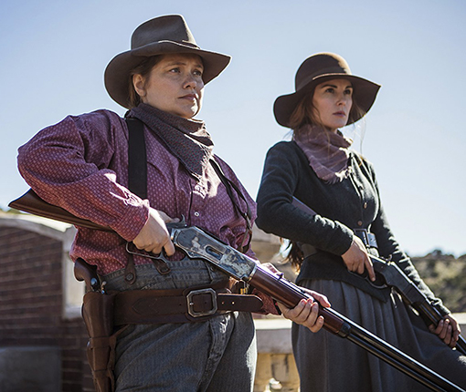 Two women in old traditional Western garb, holding shotguns.