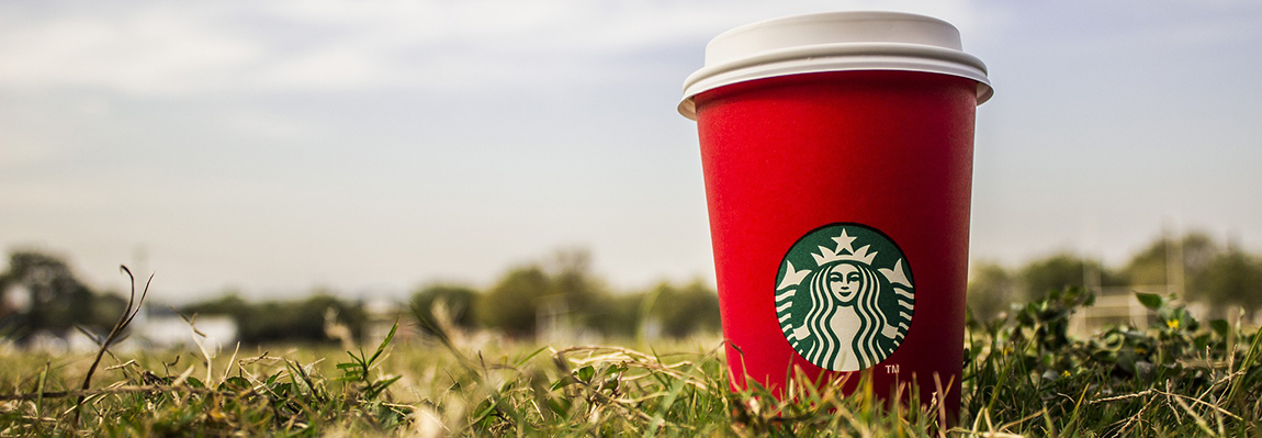 A red holiday Starbucks cup on a grass field.
