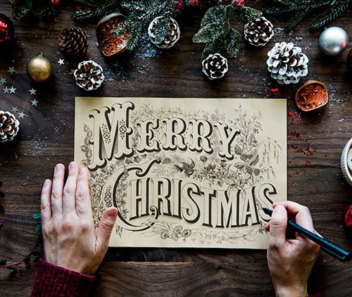 Someone using calligraphy to make a Holiday card