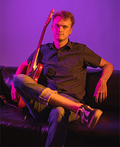 Alex Sundstrom sitting on couch with guitar